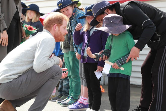 1. Meghan and Harry kneel down to talk to kids