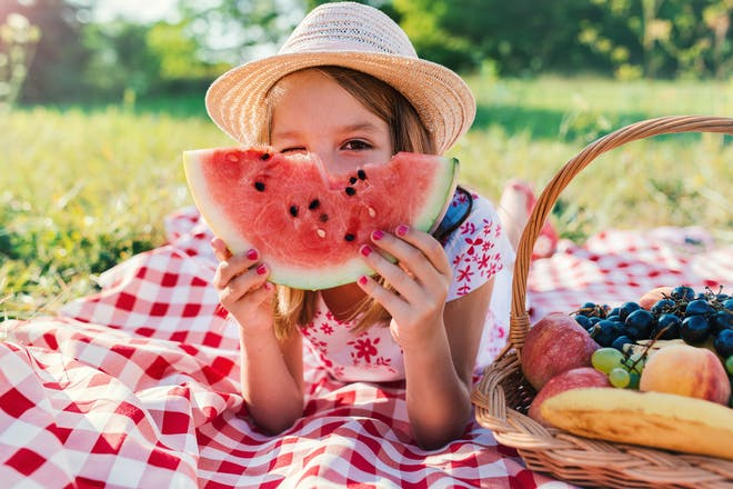 young girl at picnic holding a watermelon slice