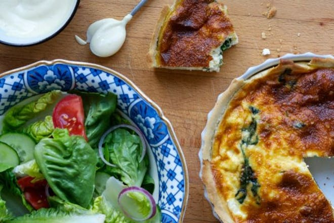 quiche next to bowl of salad