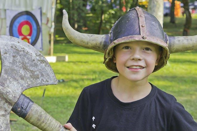Young boy wearing viking helmet holding axe