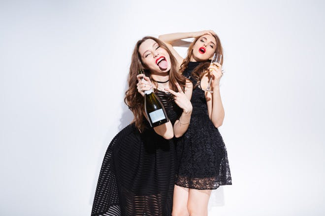 young women in party dresses with champagne