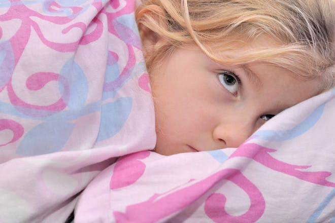little girl in bed with pink duvet