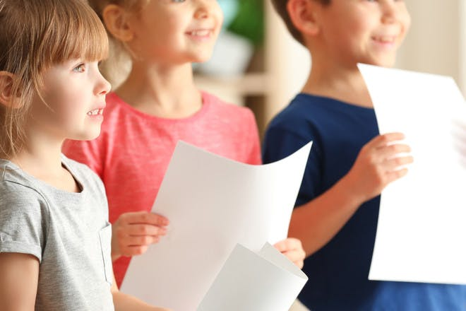 Kids singing holding pieces of paper