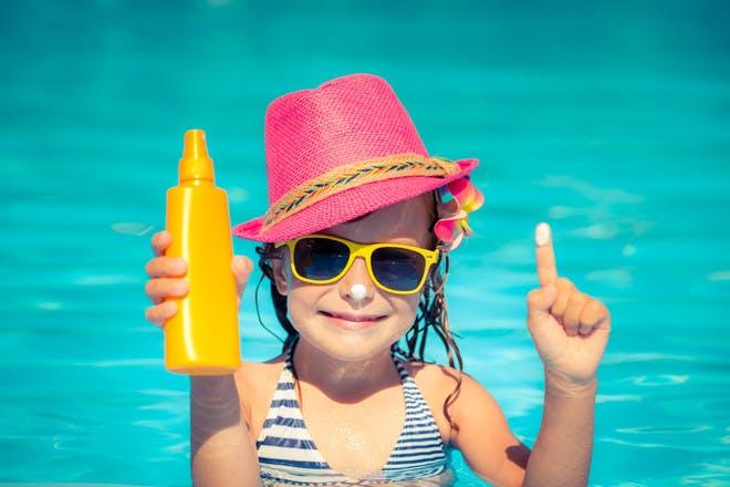 Girl with sun cream at beach