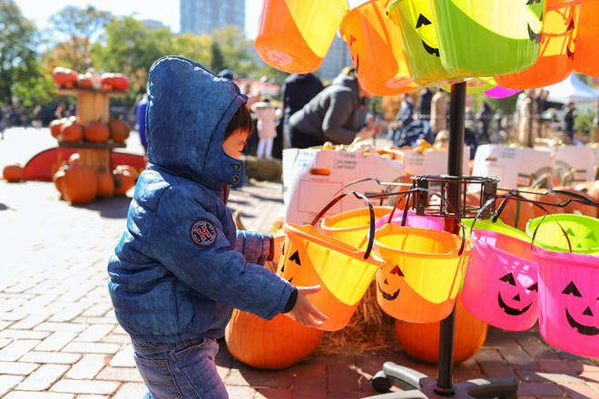A toddler in a duffel coat picks out a trick or treat bucket at a Halloween festival