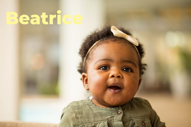 Smiling baby with bow in hair. Name Beatrice written in text