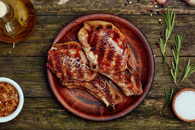 Grilled pork rib chop with mustard, salt and rosemary.