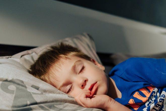 Little boy asleep in bed