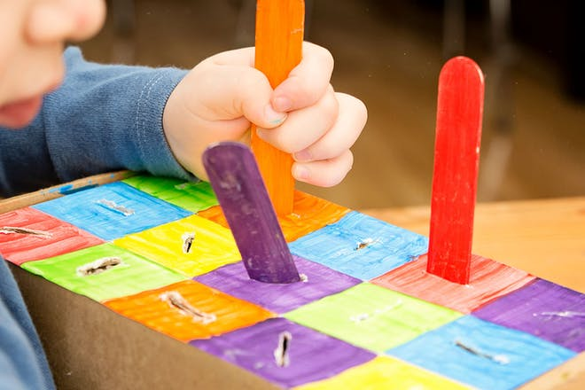 Child placing coloured lolly sticks into a homemade colour sorter toy