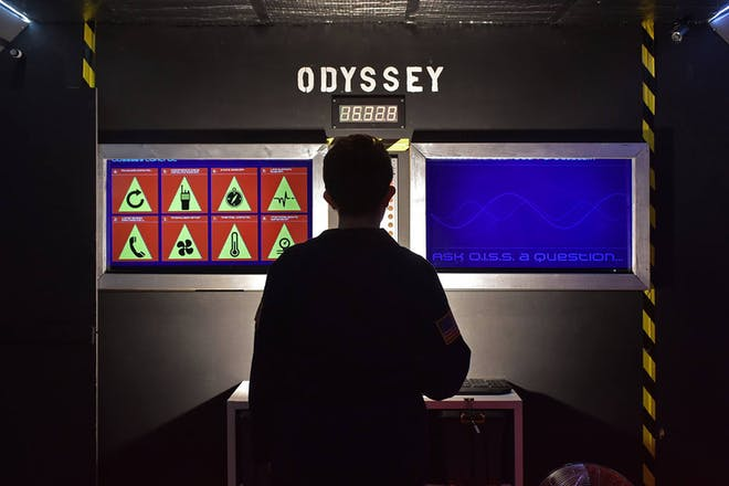 Person in front of two computer screens in an escape room