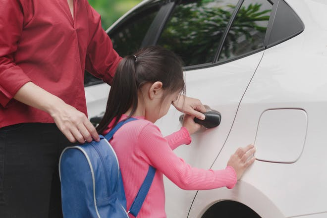 Girl with back pack opening car door