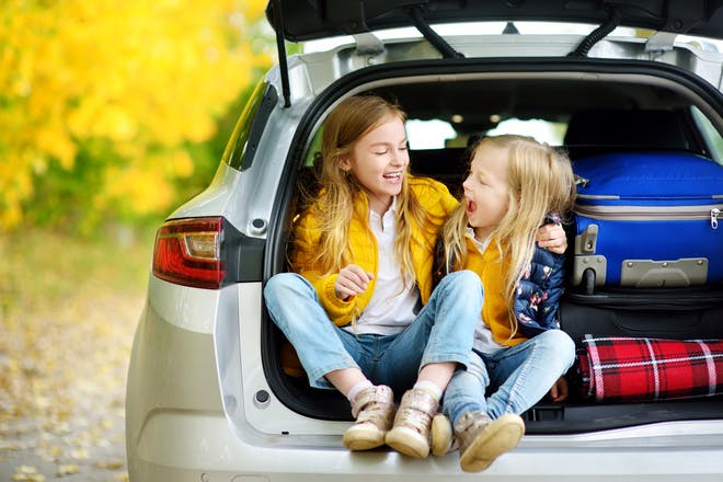 two girls sitting in open car boot