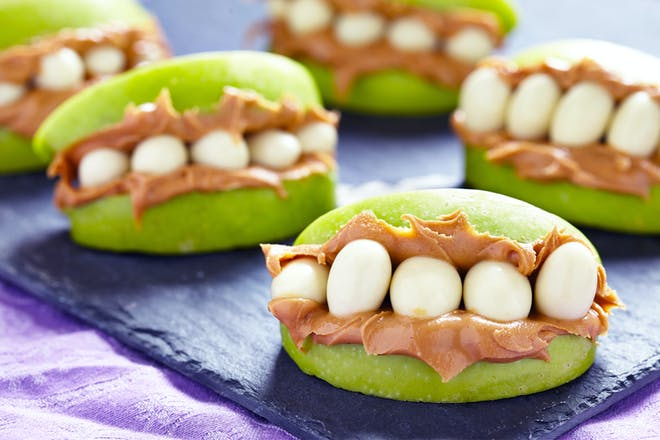 Monster mouth Halloween snacks made from apples, peanut butter and yoghurt raisins