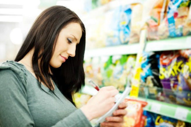 woman ticking off items on list in shop