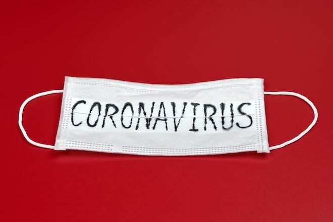 The word coronavirus written on a face mask
