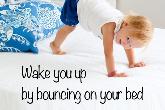 child doing handstand on bed