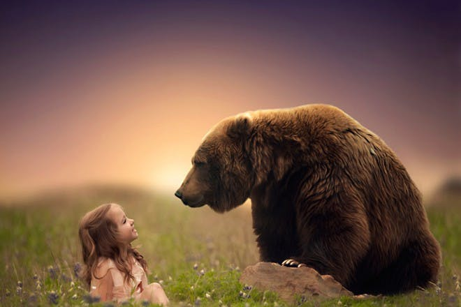 girl sitting in field looking up at brown bear