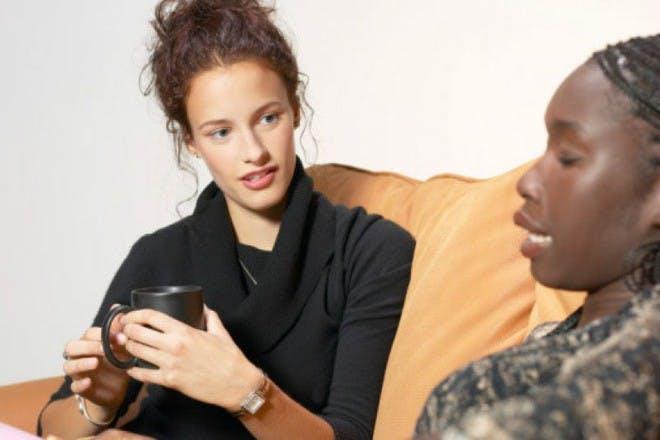 two women sitting on sofa talking