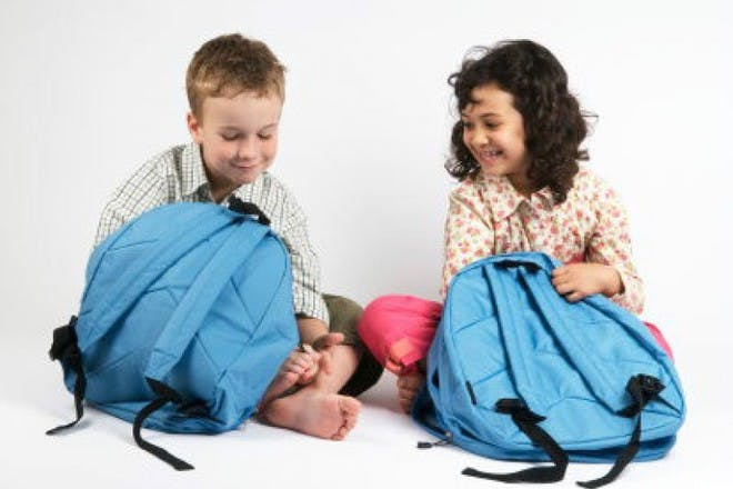 boy and girl sitting with school bags