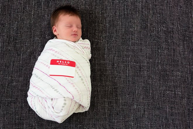 Swaddled baby with name tag