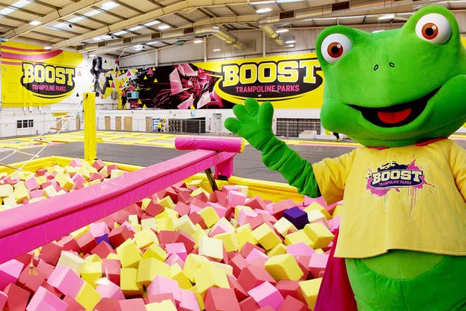 Frog mascot standing by foam pits at Boost trampoline park