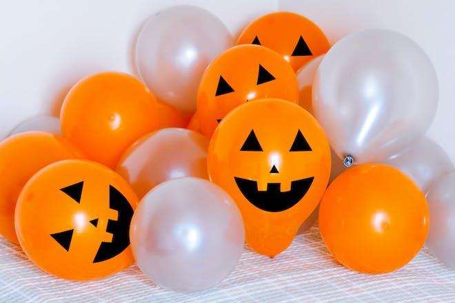 Orange halloween balloons with pumpkin faces drawn on