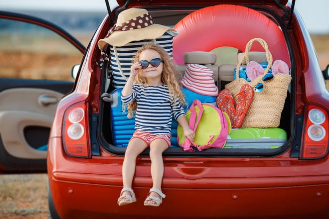 Child in boot of car with holiday packing