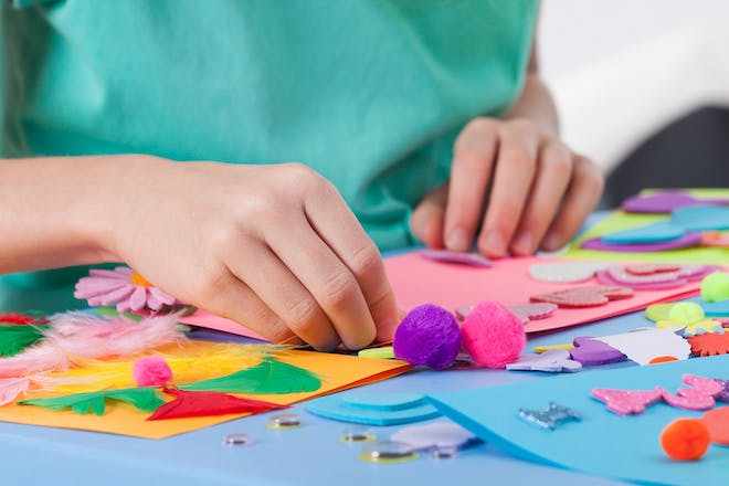 Child crafting with pom poms and feathers