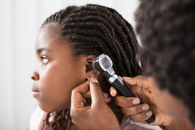Child with ear infection being seen by a doctor