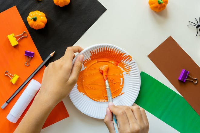 White paper plate painted orange for Halloween craft