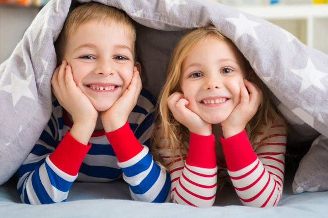 Kids in pyjamas under duvet