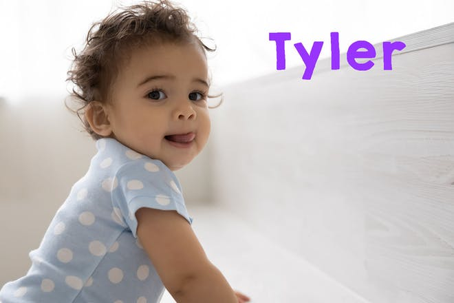 Baby in spotty t-shirt trying to stand. Text says Tyler