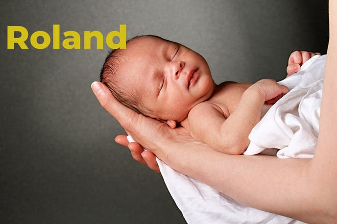 Sleeping baby being held in mum's arms. Name Roland written in text