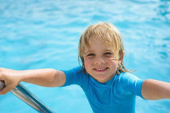 Blond haired boy climbing up the steps of swimming pool