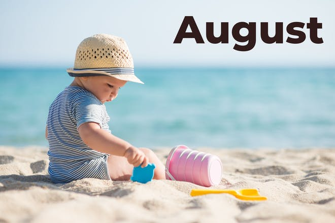 Baby sat on the beach with August written in text