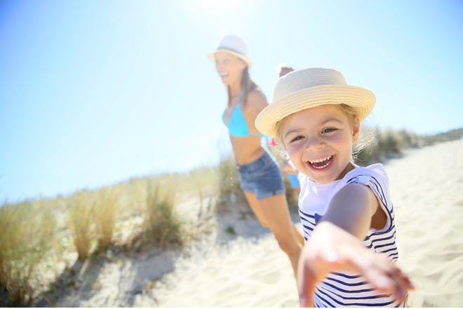 smiling girl on a beach with her mum