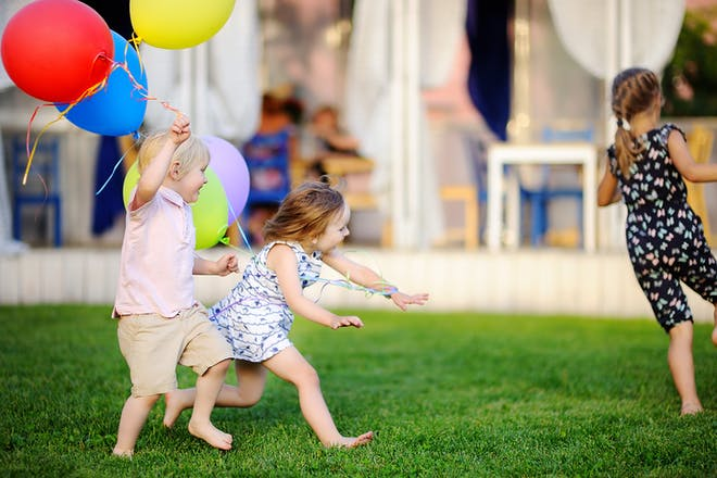 young children playing tag in garden holding balloons
