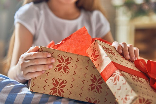 A child unwrapping a Christmas present box