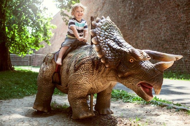 little boy with plastic dinosaur