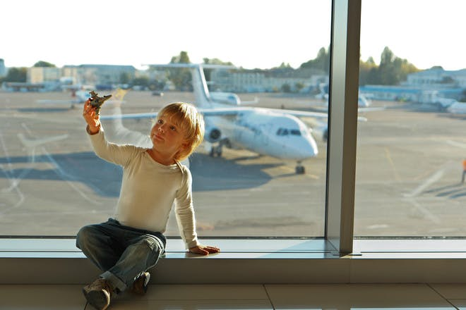 little boy with toy plane at airport