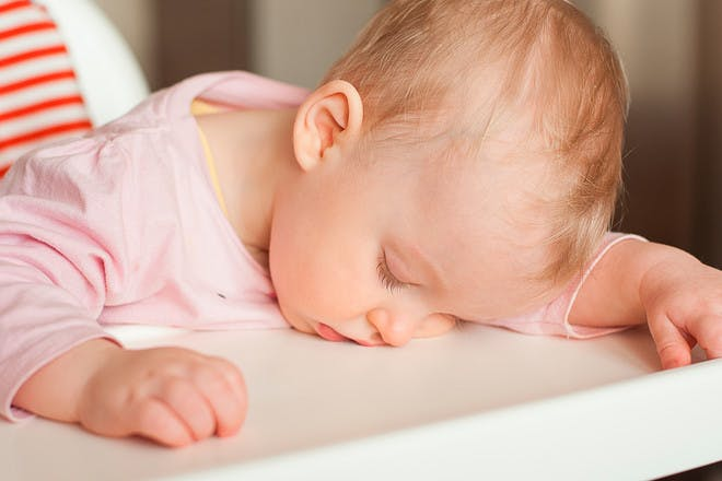 Baby asleep in highchair during weaning