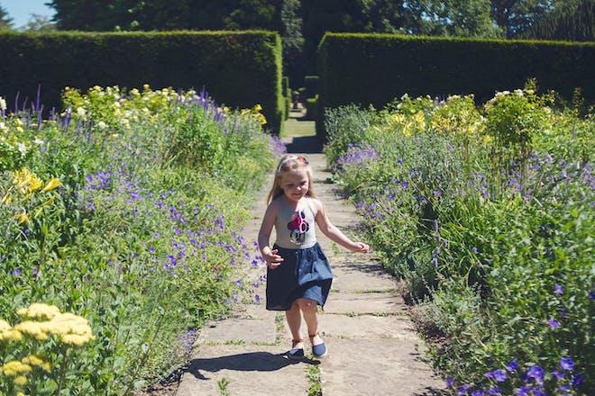 Girl running through gardens