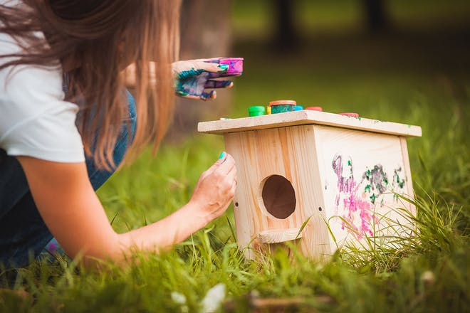 Young girl painting a wooden bird house in the garden