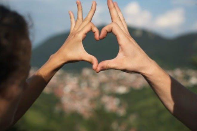 hands making heart shape outdoors
