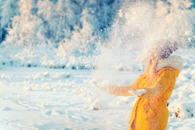 woman in yellow coat throwing snow into the air while outdoors