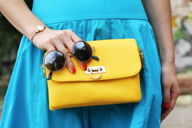 woman holding yellow clutch bag