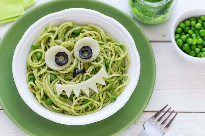 Bowl of pasta with pesto and peas and face made out of cheese and olives