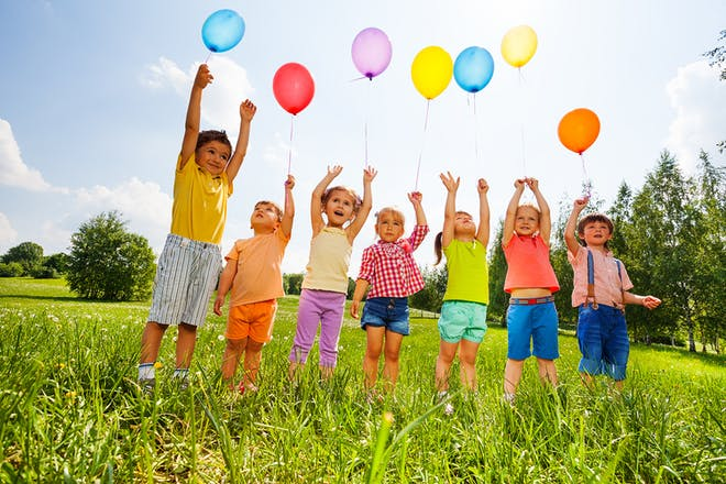 Kids playing with balloons in a field
