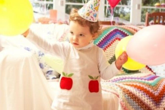 child in party hat at party with balloons
