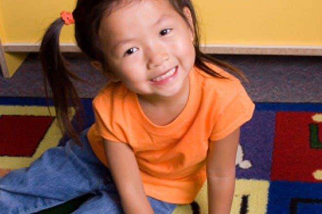 girl in orange top smiling